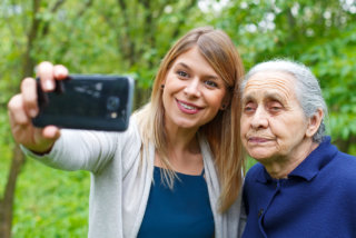 caregiver and senior woman taking picture